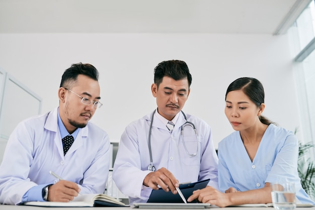Three male and female medical professionals discussing medical history of patient
