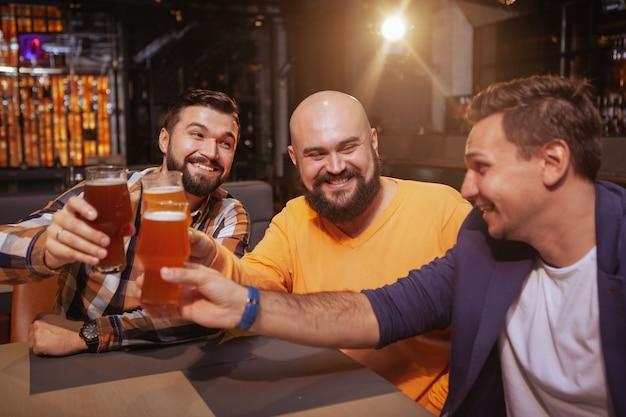 3人の男性の友人がパブでビールグラスを一緒にチリンと笑って