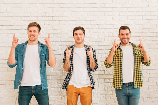 Three male friends standing against white wall pointing finger upward looking at camera