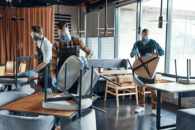 Трое мужчин-официантов в защитной спецодежде расставляют мебель в ресторане