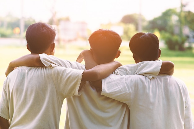 Three man hugging at sunset.concept of best friends.
