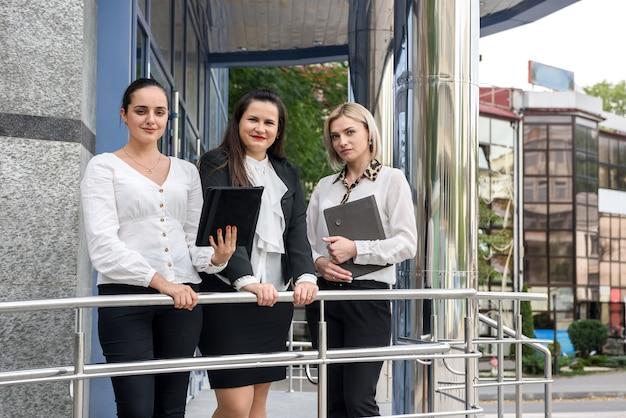 Три менеджера с папками позируют возле офисного здания