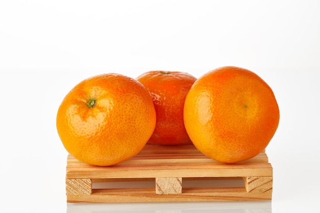 Три мандарина на логистическом поддоне в ожидании транспортировки к месту назначения, изолированному на белом фоне.