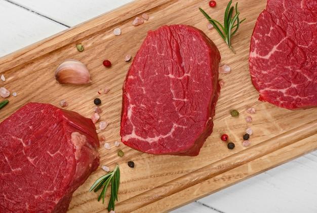 갈색 오크 나무 커팅 보드에 향신료를 곁들인 마블링 생 안심 필레 미뇽 쇠고기 스테이크 3개