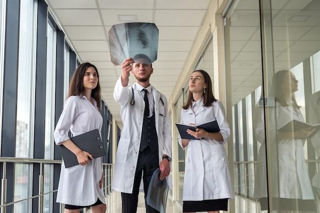 クリニックでcovid-19患者のウイルス性肺炎の肺のx線画像を通して見ている3人の医療インターン。医療コンセプト