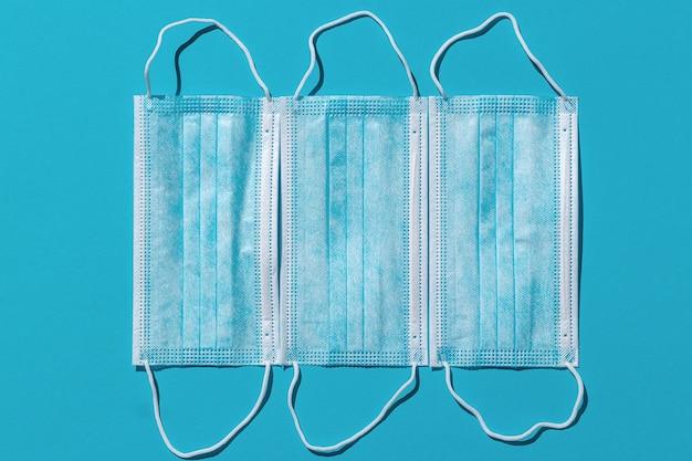 明るい青色の背景に分離された3つの医療マスク