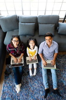 Three members of diverse family, caucasian father and asian mother and little half daughter sitting together in house living room and using 3 laptop notebook computers. idea for working at home.