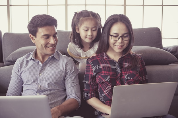 Three members of diverse family, caucasian father and asian mother and little half daughter sitting together in house living room and using laptop notebook computers. idea for working at home.