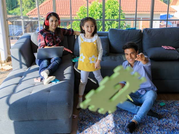 Three members of mixed races family, father, mother and kid daughter live together in home living room. girl throwing toy with dad while mom working with notebook computer. idea for work at home.