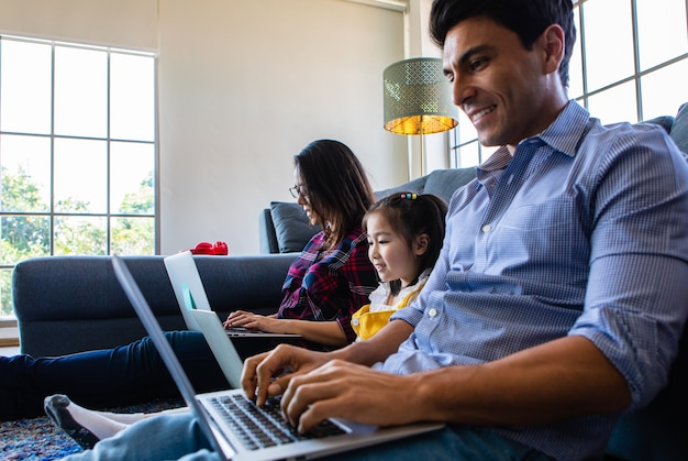 다양한 가족의 세 구성원인 백인 아버지와 아시아인 어머니, 작은 반 딸이 집 거실에 함께 앉아 3대의 노트북 컴퓨터를 사용합니다. 집에서 일하기 위한 아이디어.