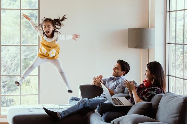 다양한 가족의 세 구성원인 백인 아버지, 아시아인 어머니, 작은 반 딸이 집 거실에서 함께 시간을 보냅니다. 엄마 아빠가 집에서 일하고 기운을 내는 동안 소파에서 점프하는 소녀.