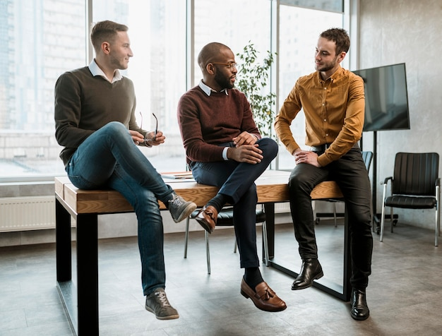 Three men conversing in the office during a meeting
