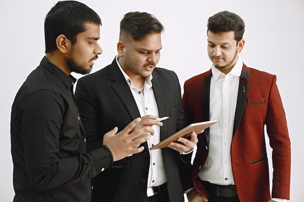 아이디어를 논의하는 세 남자. 흰 벽. 인도 국적.
