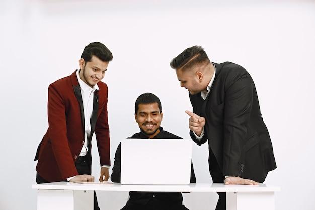 アイデアを話し合う3人の男性。白い壁。インド国籍。
