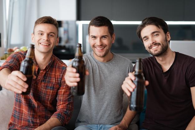 Three men drink beer. guys happy together.