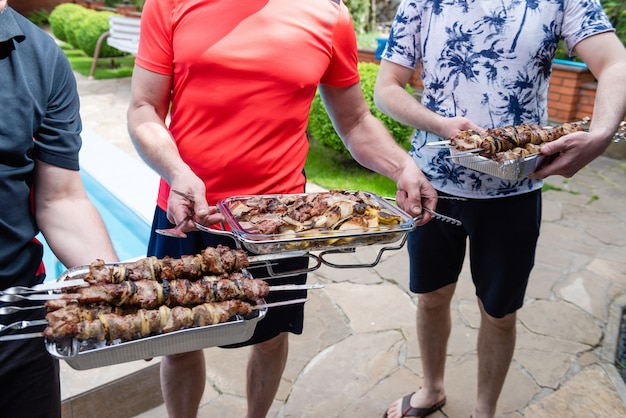 Three men holds dishes with grilled meat