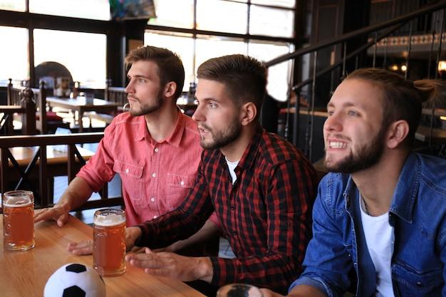 평상복 차림의 세 남자가 펍의 바 카운터에 앉아 축구를 응원하고 맥주 한 병을 들고 있다.