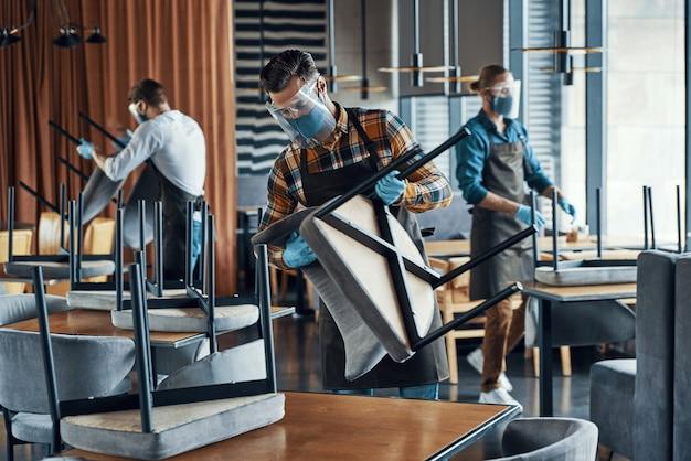 Трое мужчин в защитных масках и фартуках расставляют мебель в ресторане