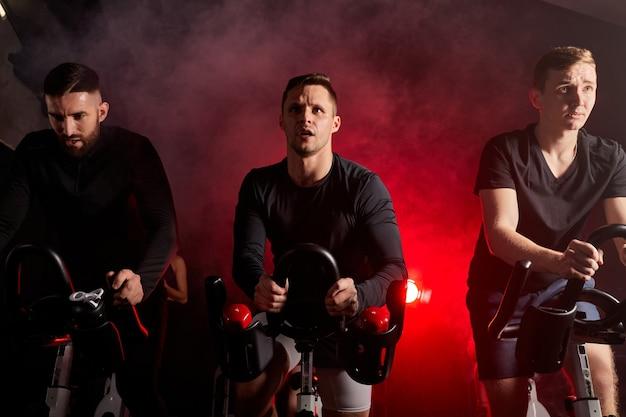 연기가 자욱한 붉은 네온 조명 공간에 고립 된 체육관에서 심장 운동 세션 동안 고정식 자전거를 함께 타는 세 남자