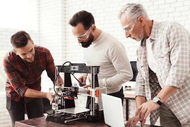 Three men set up a self-made 3d printer .
