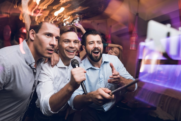 Three men sing at karaoke club. people have fun in nightclub
