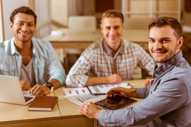 세 남자가 테이블에 앉아 카메라를 위해 포즈를 취합니다.