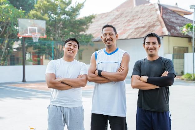 屋外バスケットボールコートの端に立っている3人の男性