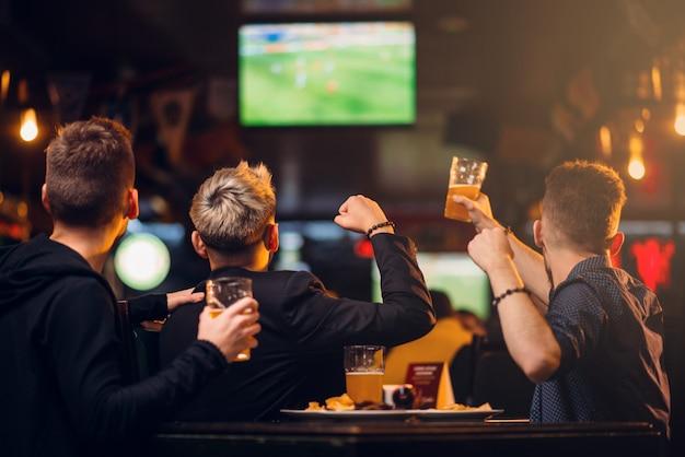 Трое мужчин смотрят футбол по телевизору в спорт-баре, счастливого отдыха фан-компании