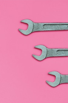 Three metallic spanners lie on texture background of fashion pastel pink color paper in minimal concept