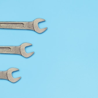 Three metallic spanners lie on texture of fashion pastel blue color paper