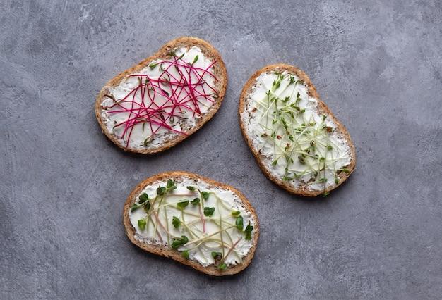 Три микро-зеленые бутерброды на сером фоне