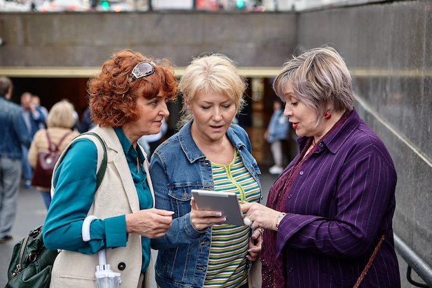 Three middle-aged ladies are discussing pictures on screen of  tablet pc while standing near underpass at daytime.