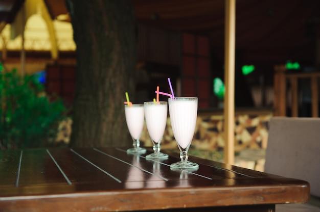 3つのミルクセーキと木製のテーブルのスムージー