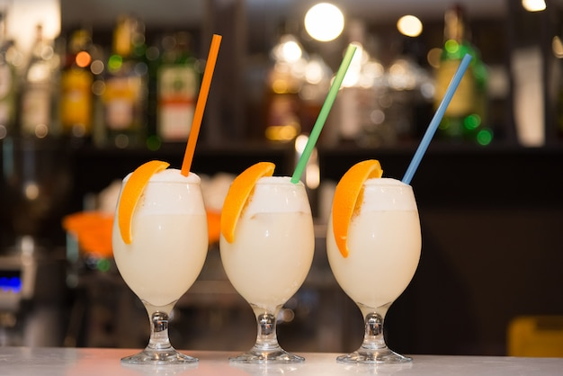 Three milkshakes with orange and straws stand on the bar counter