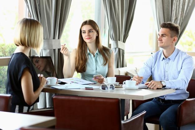 Three millennial people portrait met in cafe