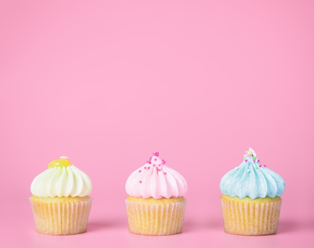 Three mini pastel cupcakes on pink copy space