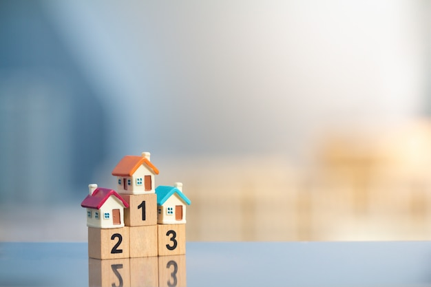 Three miniature houses on winner podium on modern cityscape background