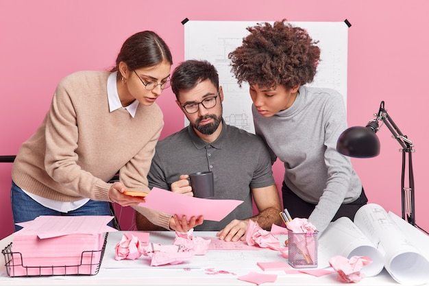 Three mixed race office coworkers collaborate on new building project look attentively in paper with information surrounded by sketches blueprints discuss ideas for illustation pose at coworking space