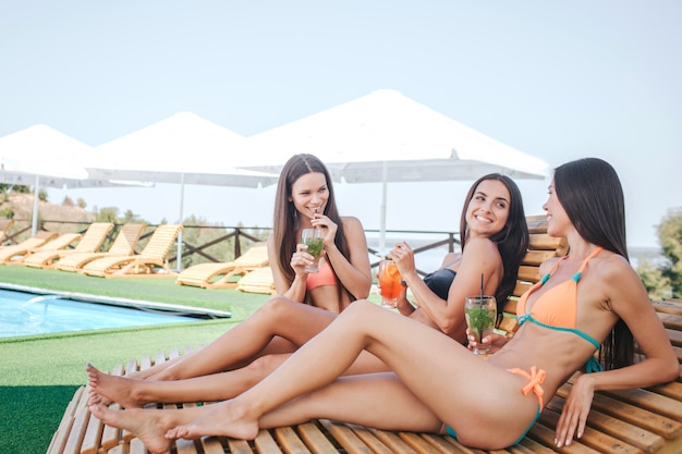 앉아서 sunbeds에 누워 세 가지 모델입니다. 차가워 요 청녀들은 칵테일을 마시고 휴식을 취합니다. 모델은 서로를 봅니다. 그들은 함께 시간을 보냅니다.