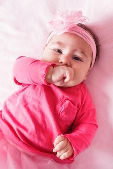 3개월 된 아기가 주먹을 빨고 있다.