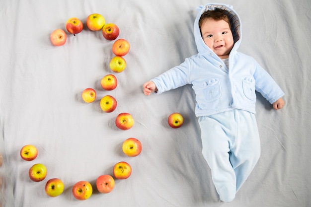 Three month old baby. three month old baby, on a gray background. laid out the figure three of apples.