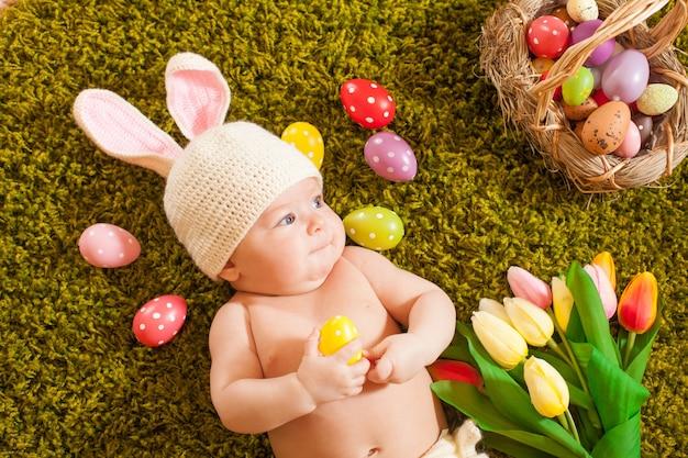Трехмесячный ребенок лежал на ковре из травы как пасхальный кролик