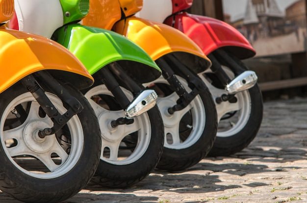 Three mopeds painted in red green yellow colors