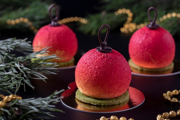 暗い背景にクリスマスボールの形をした3つのムースデザート。新年会。水平フォーマット