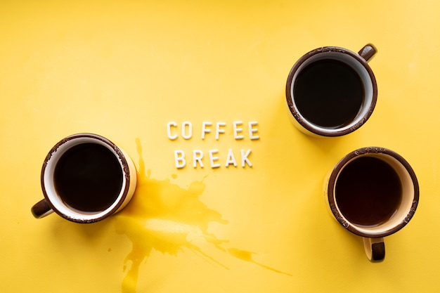 Three mugs of espresso on a yellow background with the inscription coffee break and a spilled puddle of coffee.