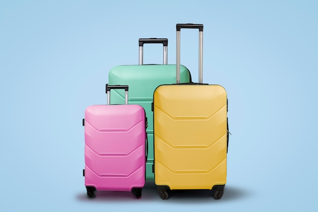 Three multi-colored plastic suitcases on wheels on a blue background. travel concept, vacation trip, visit to relatives