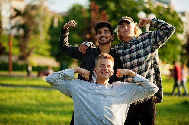 3人の多民族の男が屋外でポーズをとりました。