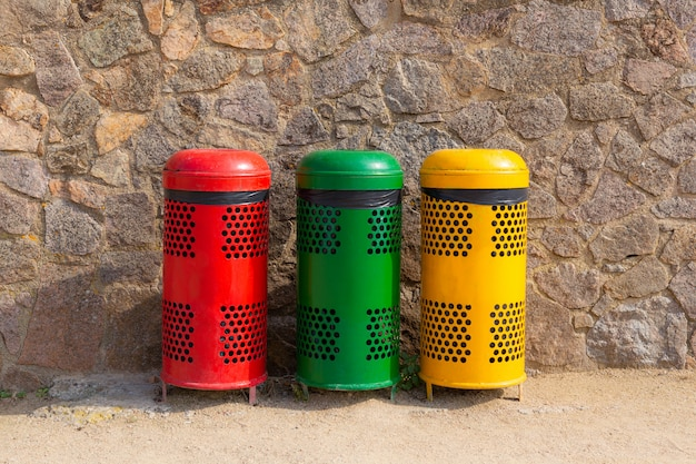 Three multicolored recycle bins for waste near the wall. sort waste