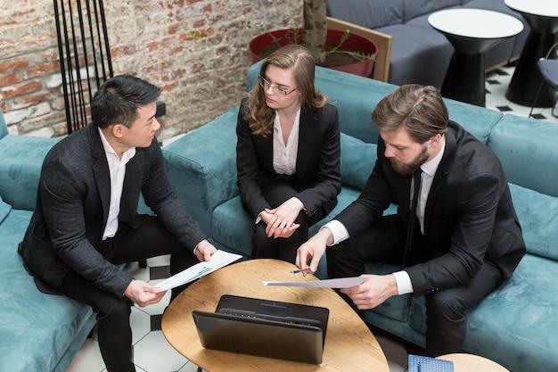 Три многонациональных бизнесмена рассматривают предложение бизнес-контракта в области ит-технологий и оказания юридических консультационных услуг.