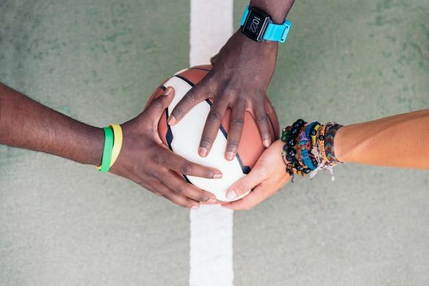 手を積み重ねる3人の多民族の友人。